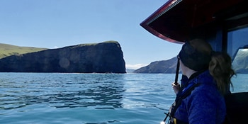 Woman on boat tour watching Akaroa coastline